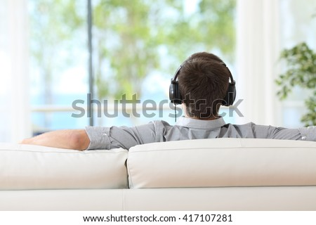 Back view of a man relaxing and listening music with headphones sitting on a couch and looking through the window at home - stock photo