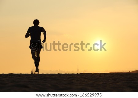Back view of a man running on the beach at sunset with the horizon in the background