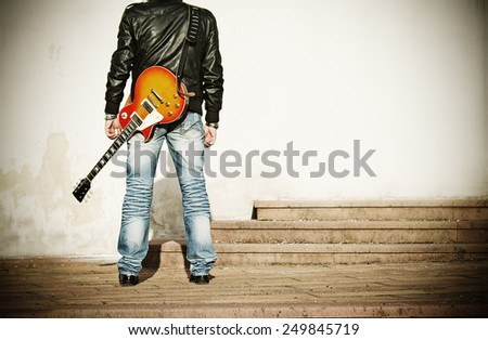 back view of a man with a guitar on his shoulder - stock photo