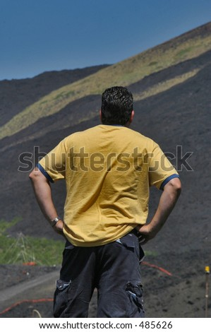 Back view of a man with his hands on his hips looking at a volcano - stock photo