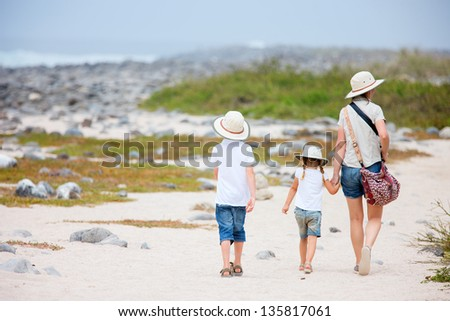 Back view of a mother and two kids hiking on Galapagos island of North Seymour - stock photo