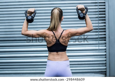 Back view of a muscular woman lifting kettlebells - stock photo