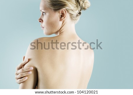 Back view of a nude blond woman looking ahead against a blue background. - stock photo