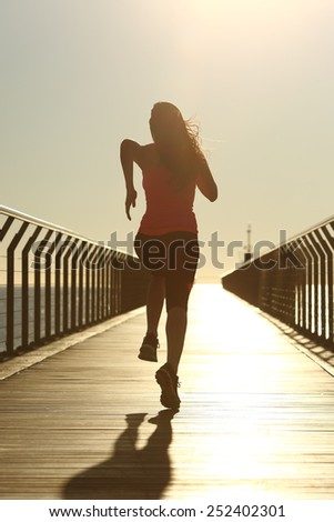 Back view of a runner silhouette running fast at sunset on a bridge on the beach - stock photo