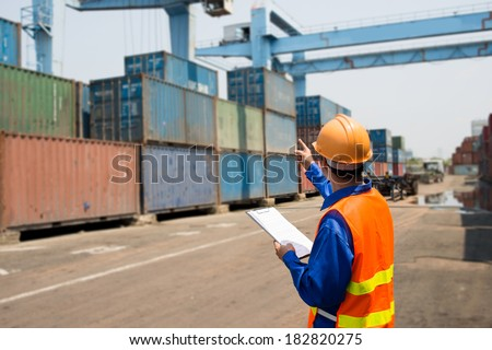Back view of a seaport inspector busy with in-checking  - stock photo