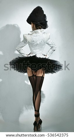 Back view  of a sensuality ballerina in a black tutu, stocking, hat and white jacket