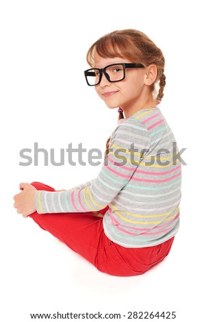 Back view of a smiling little girl in eyelgasses sitting on the floor looking at camera over shoulder, isolated on white background - stock photo