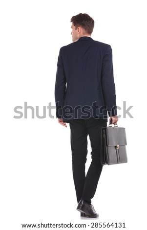 Back view of a tall business man walking while holding his briefcase. - stock photo