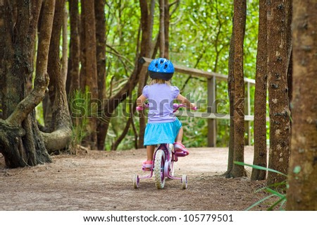 Back view of a toddler girl riding a bike in the forest - stock photo