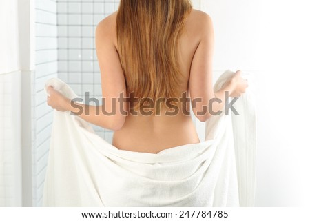 Back view of a woman body entering in the shower with a white towel - stock photo