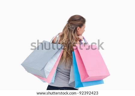 Back view of a woman holding shopping bags against a white background