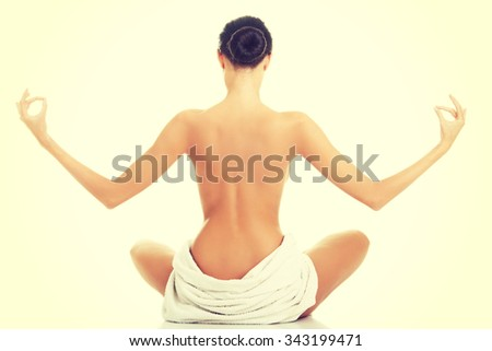 Back view of a woman in towel practising yoga. - stock photo