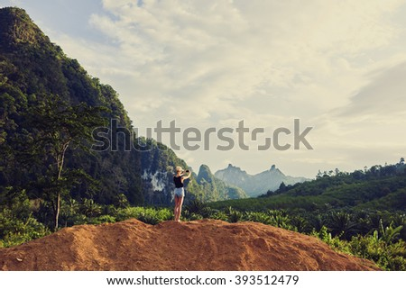 Back view of a woman is shooting video on cell telephone during summer vacation with daughter in Latin America. Female is taking photo with smart phone camera, while is standing against jungle scenery - stock photo