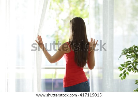 Back view of a woman looking outdoors through a window and opening curtains at home - stock photo