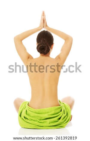 Back view of a woman practising yoga, wrapped in towel. - stock photo