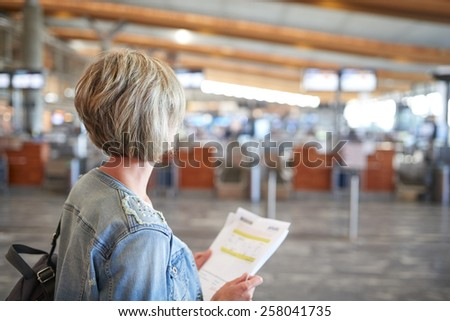 Back view of a woman standing in airport hall, holding sheets of e-tickets - stock photo