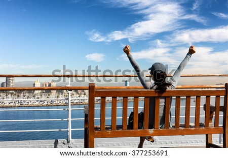 Back view of a woman stretching while sitting on bench and looking out into bay from public walkway.  - stock photo