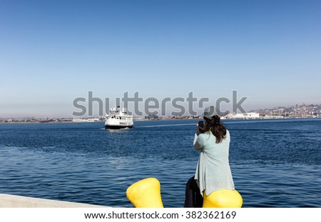 Back view of a woman taking photos with cell phone of San Diego bay in Southern California while sitting down at pier.  - stock photo