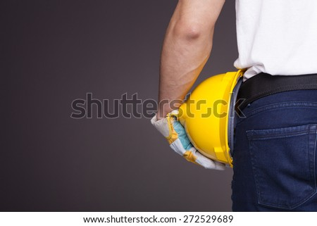 Back view of a worker holding a helmet against grey background - stock photo
