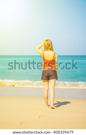 Back view of a young beautiful woman tropical beach - stock photo