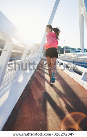 Back view of a young brunette athletic woman with perfect slender figure running on the bridge against sunset, sporty female dressed in sportswear jogging in the fresh air during her recreation time - stock photo
