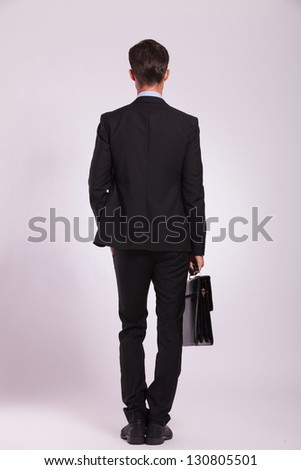 back view of a young business man standing with a hand in the pocket and holding his briefcase with the other, on gray - stock photo