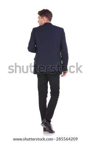 Back view of a young business man walking while looking to his side.