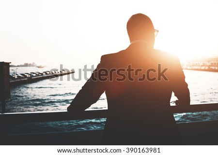 Back view of a young businessman is enjoying view and rest after meeting during his business trip. Silhouette of a male lawyer is resting after work day, while is standing outdoors against sunset - stock photo