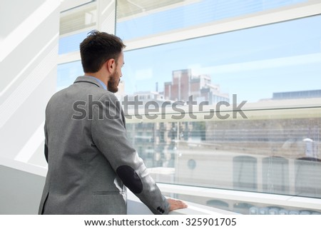 Back view of a young businessman thinking about something while looking in big office window, confident serious men managing director dressed in formal wear enjoying calm after hard work day  - stock photo