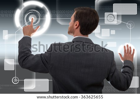 Back view of a young businessman working on a big touchscreen - stock photo