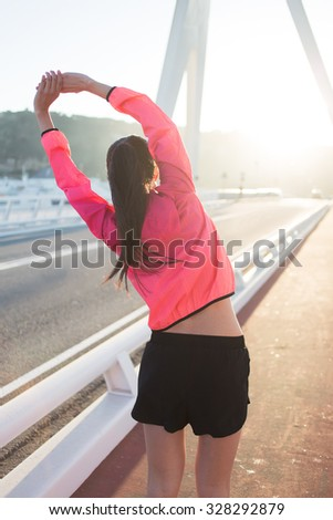 Back view of a young female jogger dressed in bright sportswear doing arms stretching exercise outdoors in summer day, athletic woman with perfect slim body working out while standing on running road  - stock photo