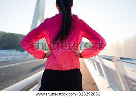 Back view of a young female runner dressed in colorful windbreaker enjoying sun and rest after evening jog, brunette sporty woman relaxing after her fitness training in the fresh air during free time  - stock photo