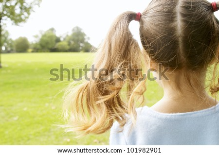 Back view of a young girl looking at horizon and wearing two ponytails in the park - stock photo