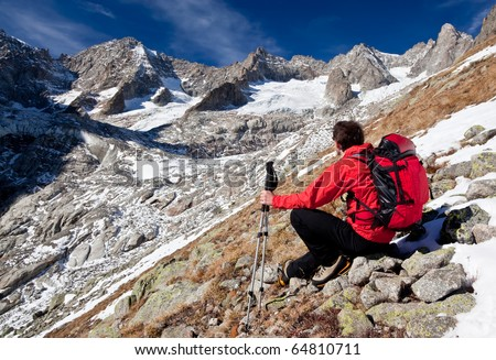 Back view of a young male hiker while observing a high mountain panorama. Sitting position, red jacket, black pant. Triolet glacier, Mount Blanc massif, Italy, Europe.