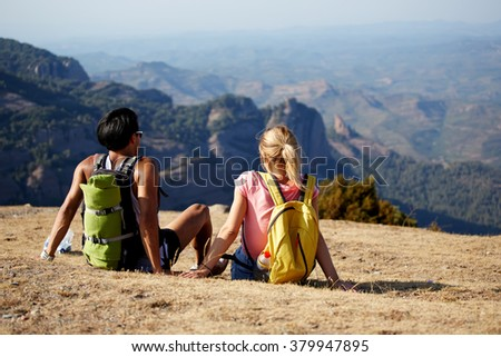 Back view of a young man and woman enjoying amazing view while sitting on a high mountain in sunny day, two travelers resting after walking in highlands during their the long awaited summer journey - stock photo