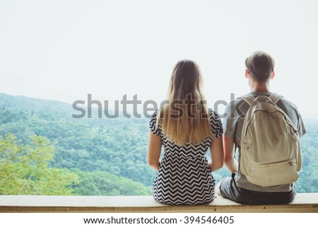Back view of a young man and woman enjoying amazing view while sitting on a high mountain in sunny day, two travelers resting. - stock photo