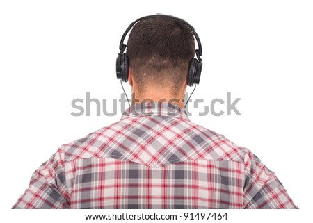 Back view of a young man listening music with headphones