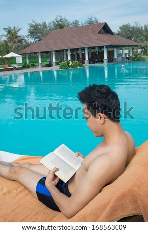 Back view of a young man lying on the chaise-lounge and reading a book near the swimming pool - stock photo
