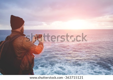Back view of a young man tourist taking photo with cell telephone digital camera while standing in front sea with waves, hipster guy with trendy look shoots video with ocean landscape on mobile phone  - stock photo