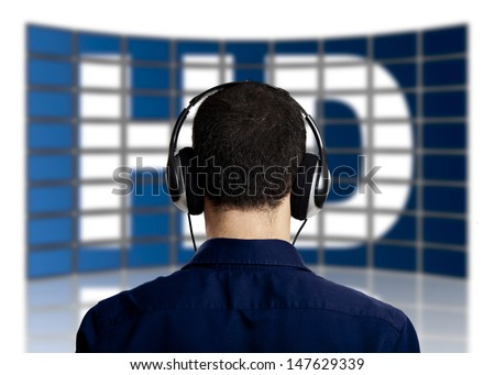Back view of a young man with head phones watching a big TV panel  - stock photo