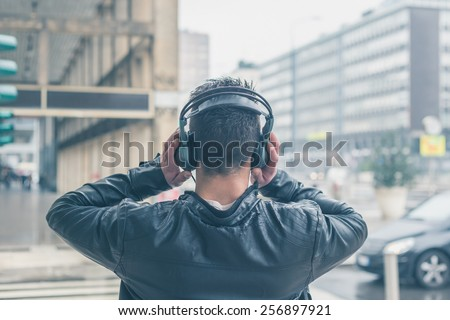 Back view of a young man with headphones listening to music in the city streets - stock photo