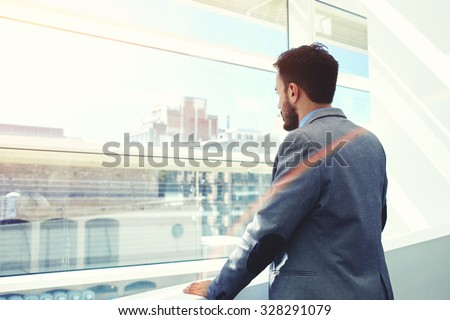 Back view of a young men entrepreneur thinking about something while looking in big office window, successful serious businessman dressed in elegant luxury clothes enjoying calm after hard work day - stock photo