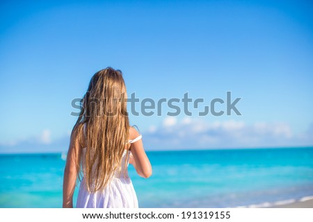 Back view of adorable little girl at white beach during summer vacation - stock photo