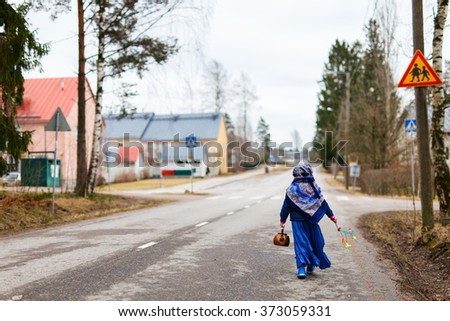 Back view of adorable little girl outdoors dressed for Easter traditional celebration in Finland - stock photo