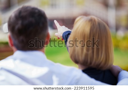Back view of affectionate couple sitting on bench and looking ahead. mature woman pointing ahead with her finger while sitting - stock photo