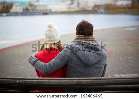 Back view of affectionate couple sitting on the bench and looking at river - stock photo