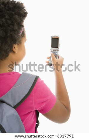 Back view of African American girl with backpack looking at cell phone. - stock photo