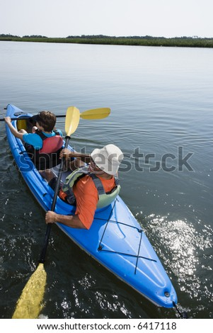 Back view of African American middle-aged couple paddling kayak. - stock photo