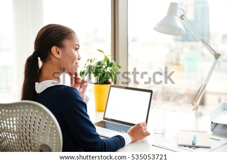Back view of african business woman in dress sitting on workplace near the window and using laptop in office