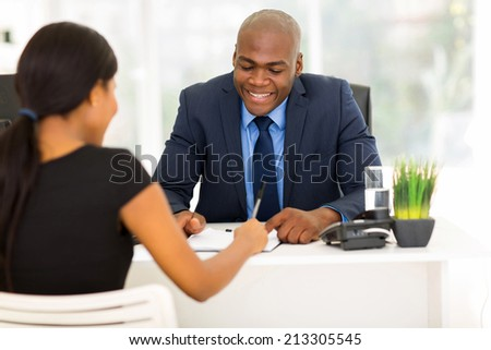 back view of african woman signing employment contract in office - stock photo